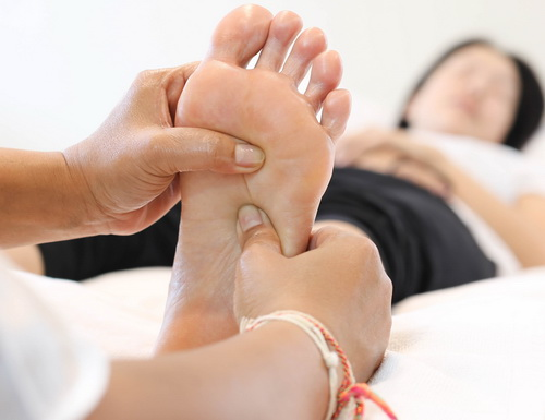 Using thumbs in reflexology and Thai foot massage