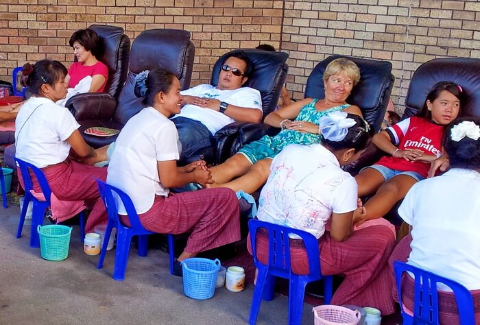 Thai Foot Massage shop with customers sitting in recliners in Thailand